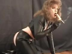 Rocker redhead in black leather and latex does some smoking
