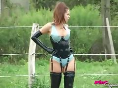 Latex fetish babes play in the dirt and grass on the farm