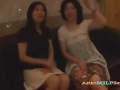 2 Mature Asian Women Sucking Guy Jerking Off His Cock On The Bed In The Hotel