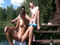 Two pornstars playing with toys outside